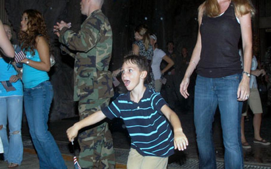 Ryan, 6, spots his father stepping out of an airplane and runs toward him Monday at Kadena Air Base.