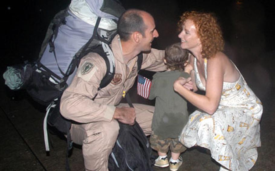 Staff Sgt. Jonathon hugs his wife and child outside a hangar at Kadena Air Base.