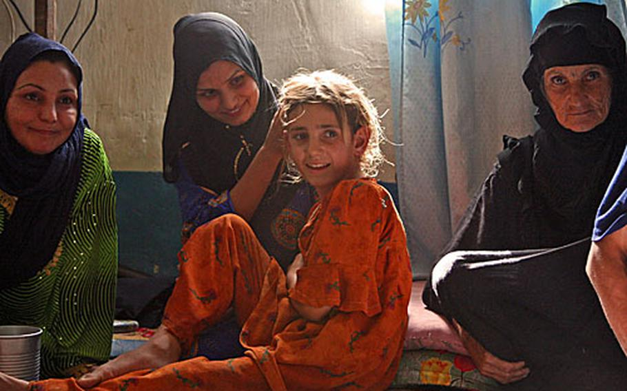 Suham Hassan Ka-Naan touches her niece's hair as a translator relays a question during an interview Sunday at their home southeast of Baghdad. Suham lost her legs during an insurgent mortar attack three years ago. Her sister (left), Hayat, was born crippled, and their niece was hit by a truck, leaving her with a severe limp.