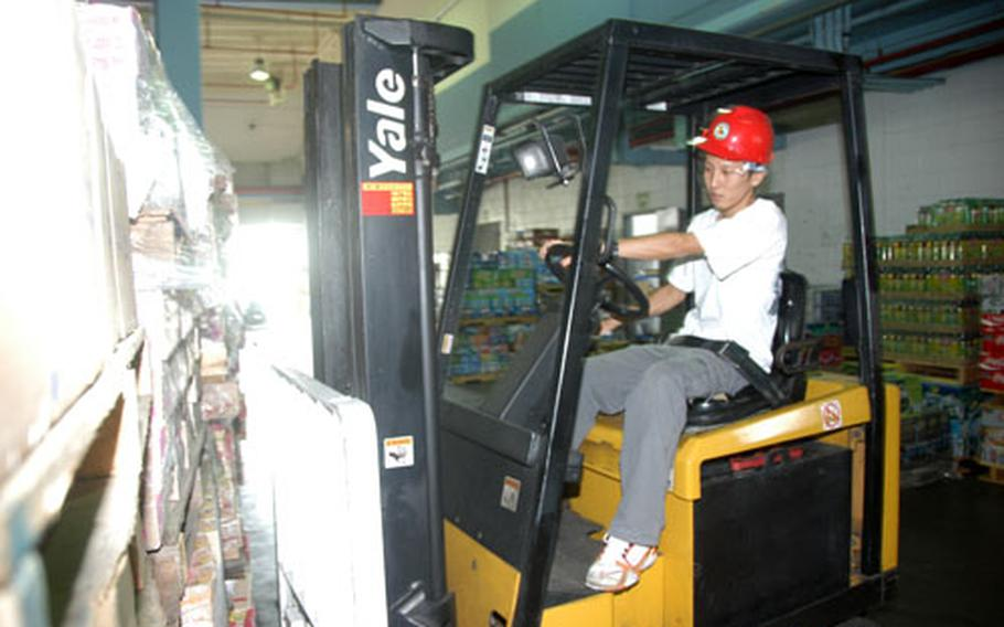 Warehouse foreman Muto Takuya operates a forklift at the Camp Foster Commissary in Okinawa. This month, commissaries worldwide will be hosting case-lot sales, with many bulk goods dramatically discounted.