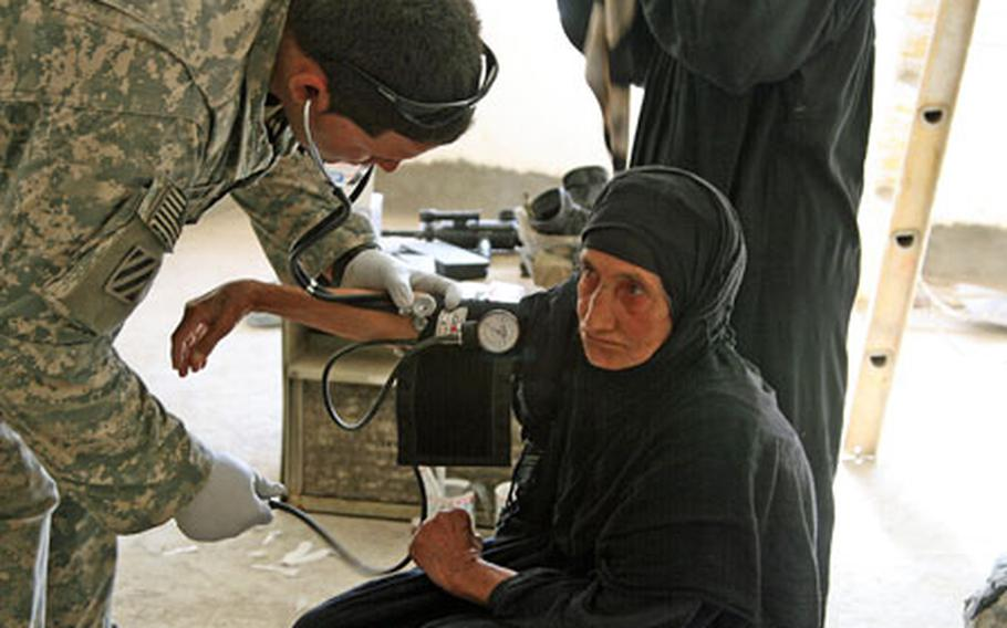 Pfc. Josue Roman, 22, of Hatillo, Puerto Rico, checks the blood pressure of an Iraqi woman during a medical relief operation Tuesday in the village of Al Arabia, on the southeastern outskirts of Baghdad. Soldiers with Troop A, 3rd Squadron, 1st Cavalry Regiment treated more than 100 villagers during the operation. At least that many were turned away for lack of time.