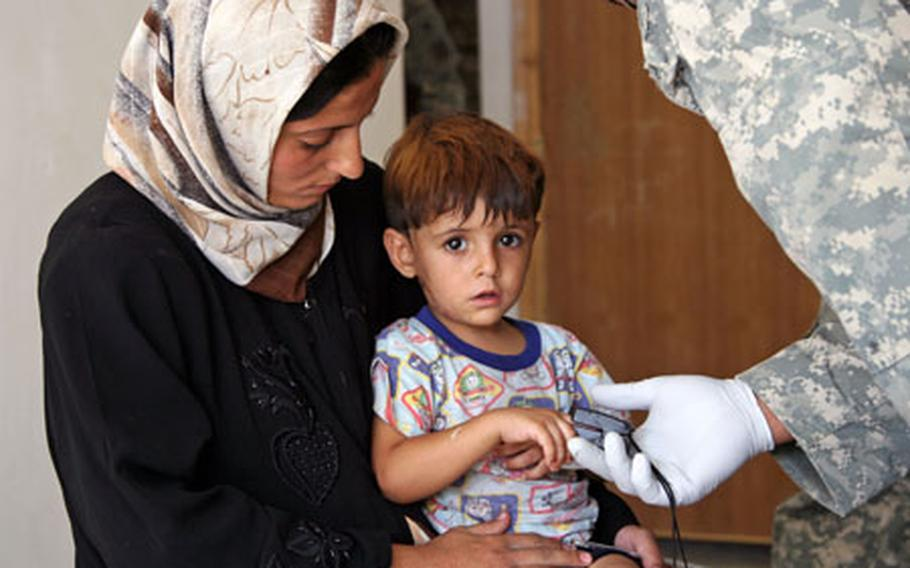 An Iraqi woman holds her young son as a U.S. Army medic checks the boy's pulse during a medical relief operation Tuesday in the village of Al Arabia, on Baghdad's southeastern outskirts.