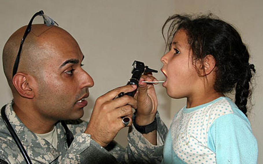 Capt. Sayed Ali, 31, of Nairobi, Kenya, tells a young Iraqi girl to open wide as he examines her throat during a medical relief operation Tuesday in the village of Al Arabia, on the southeastern outskirts of Baghdad.