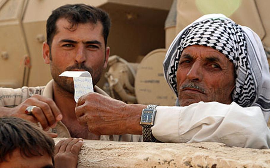 An Iraqi man holds up a bag of pills he received from U.S. troops during a medical relief operation Tuesday in the village of Al Arabia, on the southeastern outskirts of Baghdad.