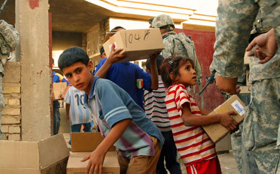 A group of Iraqi kids helps U.S. troops load boxes onto a cargo truck after a medical relief operation Tuesday in the village of Al Arabia, on the southeastern outskirts of Baghdad.