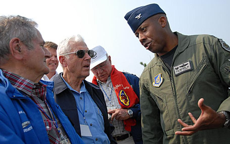 """Col. C.Q. Brown, right, commander of the 8th Fighter Wing, talks with Korean War fighter pilots Ralph Gibson, Charles Cleveland, and Wilbur """"Pete"""" Carpenter about Kunsan Air Base, South Korea."""
