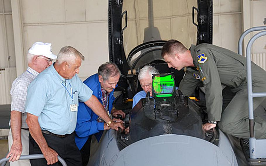 """1st Lt. Jason Curtis shows Korean War veterans and retired colonels (from left) Wilbur """"Pete"""" Carpenter, Kenneth Shealy and Ralph """"Hoot"""" Gibson and retired Lt. Gen. Charles """"Chick"""" Cleveland, seated, the interior of an F-16 fighter jet cockpit at Kunsan Air Base, South Korea."""