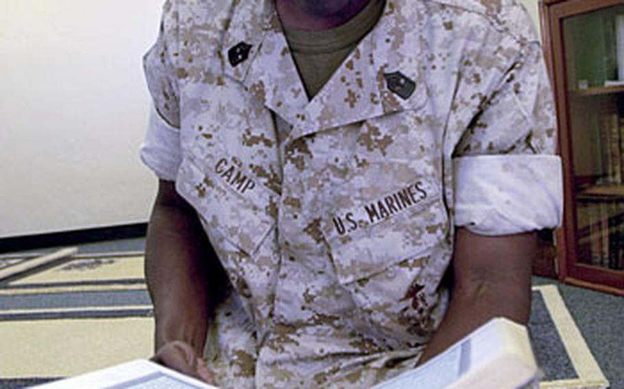 Marine Corps Master Gunnery Sgt. Hafiz Camp, 49, with Marine Wing Headquarters Squadron 1, reads the Quran at the Islamic masjhid in the Camp Foster Chapel recently.