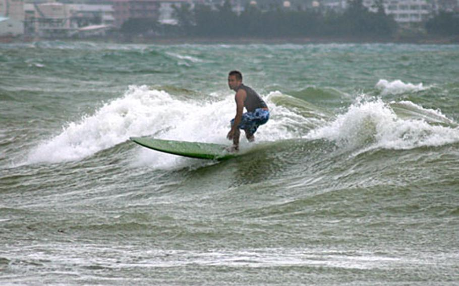 Surf's up for a local who takes advantage of the waves generated Friday afternoon by the approaching Typhoon Nari at a beach off Route 75 near Camp Courtney, Okinawa.