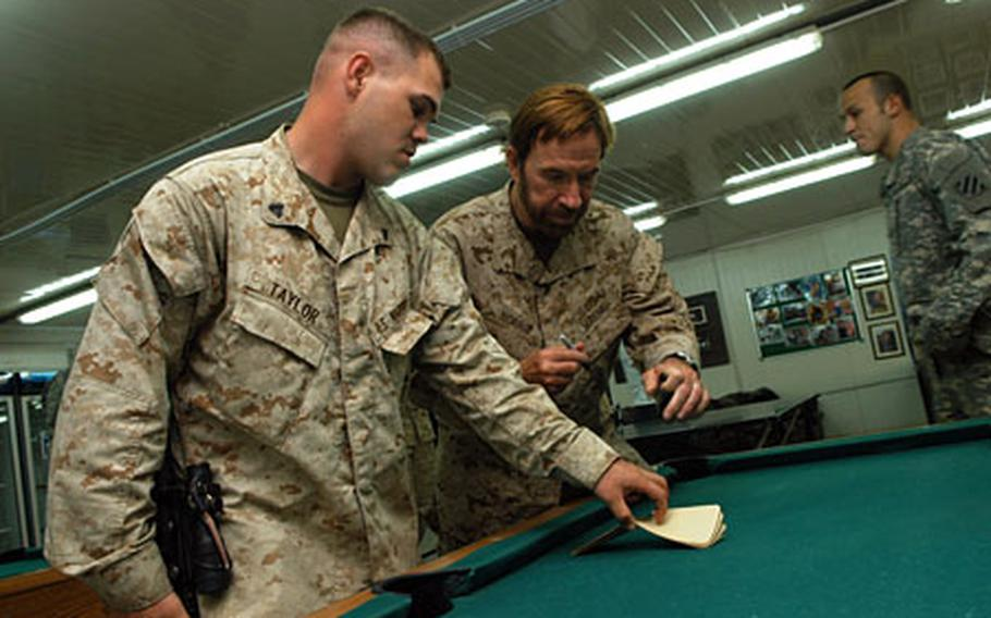 Cpl. Donald Taylor, 24, of Greenville, S.C., got some martial-arts information and a writing sample from the master himself when Chuck Norris came to Camp Blue Diamond on Friday.
