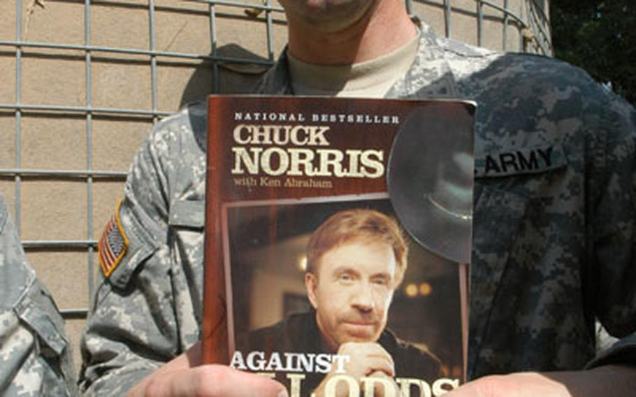 Army Capt. Eric Beltz, 27, of Jackonville, Fla., is a Chuck Norris fan from way back. He brought Norris' autobiography for Norris to sign Friday when the martial-arts star visited Camp Blue Diamond in Anbar province.