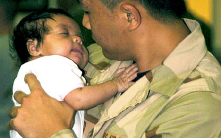 Senior Airman Vivo Jorley holds his month old daughter Jayla in the Air Mobile Command Terminal. Airmen from the 374th Airlift Wing gather in the Air Mobile Command Terminal on Yokota Air Base, Japan on Saturday. He deployed with roughly 80 airmen in support of Operation Iraqi Freedom and Operation Enduring Freedom.