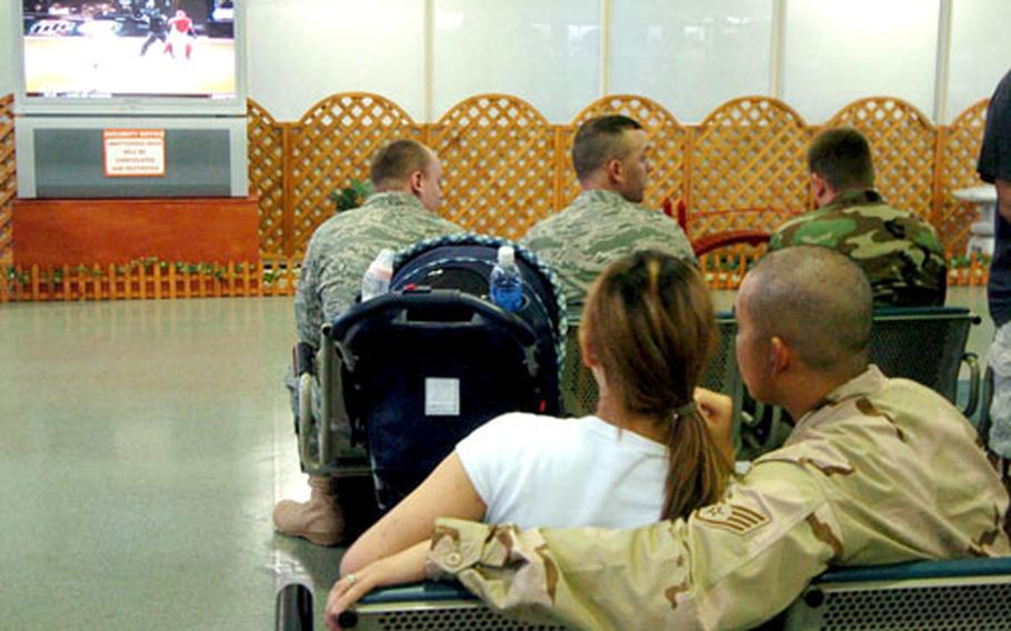Airmen from the 374th Airlift Wing watch a baseball game with their loved ones while gathered in the Air Mobile Command Terminal.