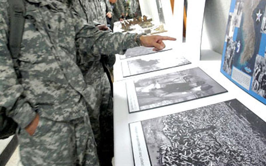 """U.S. soldiers look at photographs and artifacts from the battle of Hangyeri during the """"Staff Ride"""" for senior- and general- level U.S. and South Korean officers. Col. Eric Albert, whose father fought in the May 1951 battle, is second from the left."""
