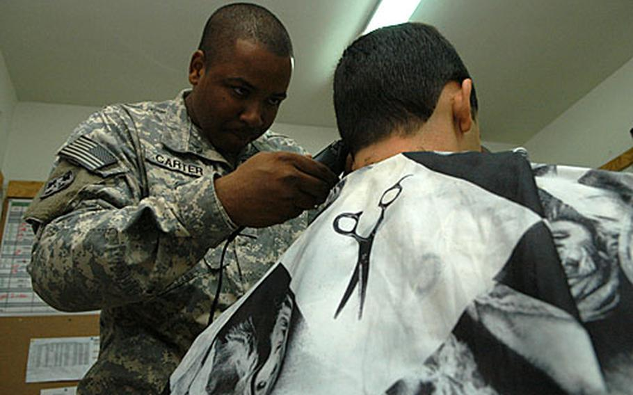 U.S. Army Sgt. Cameron Carter gives free, full service haircuts on the fly in Iraq. This is the second tour in Iraq in which the 30 year-old New Orleans native brought his clippers. He cut Lt. Carlos Alvarez's hair on Friday at Camp Blue Diamond in al Anbar province.