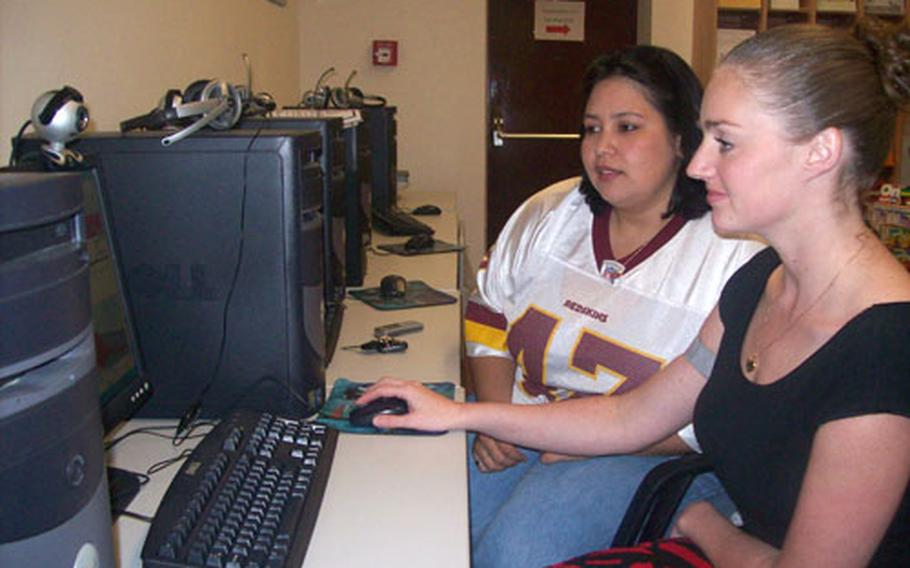 Second Cavalry Regiment spouses Nicole Heller (left) and Danielle Wilding check out equipment in the Army Community Services Yellow Ribbon room at Vilseck. The computers allow families to video conference with soldiers downrange.