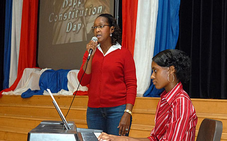 """Leisa Santiago Boetler, left, of the school bus office, sings """"My Country 'Tis of Thee"""" accompanied by junior Roberautrice Eddie on keyboards, at the Hanau Middle/High School Constitution Day ceremony."""