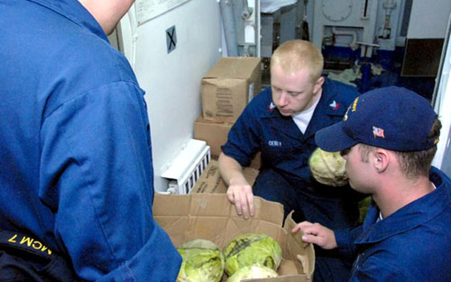 USS Patriot crew members sort cabbages Wednesday in preparation for the ship's departure, Thursday, on a several-month fall patrol. From left to right, they are Seaman Recruit Michael Kizer, Petty Officer 2nd Class Dennis Oerly and Seaman Apprentice Kyle Ames.