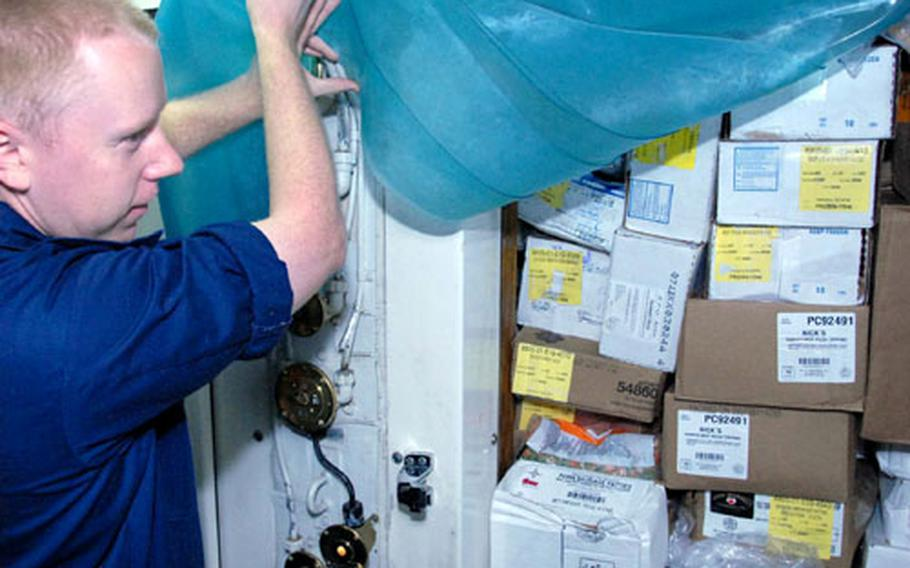 Petty Officer 2nd Class Dennis Oerly packs food into storage Wednesday on the USS Patriot.