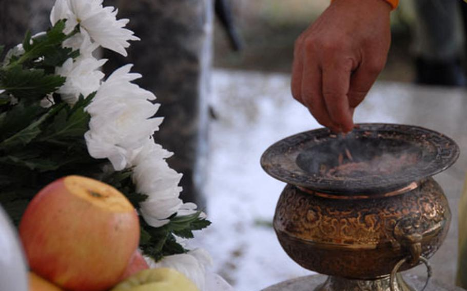 A South Korean drops incense into an urn during the ceremony.