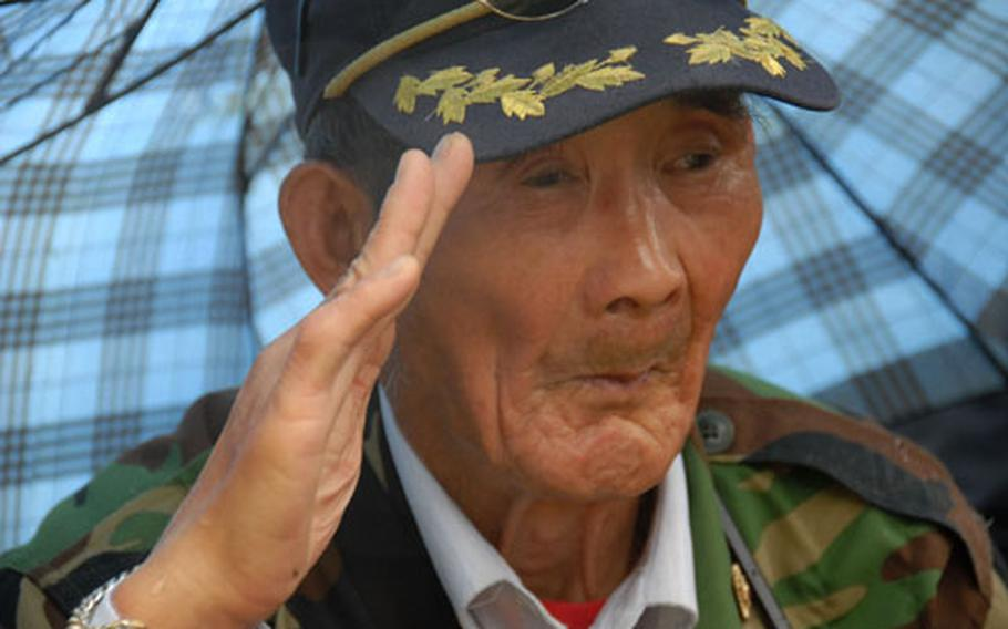 Cho Pyong-ung, 77, salutes as the Korean national anthem is played during the memorial service.
