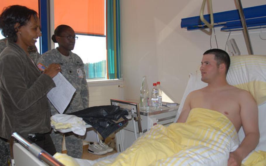 Grafenwöhr nurse case manager Helen Wise, left, and Grafenwöhr Medical Center commander Lt. Col. Telita Crosland talk to Eschenbach Hospital patient Pvt. Calvin Woods.