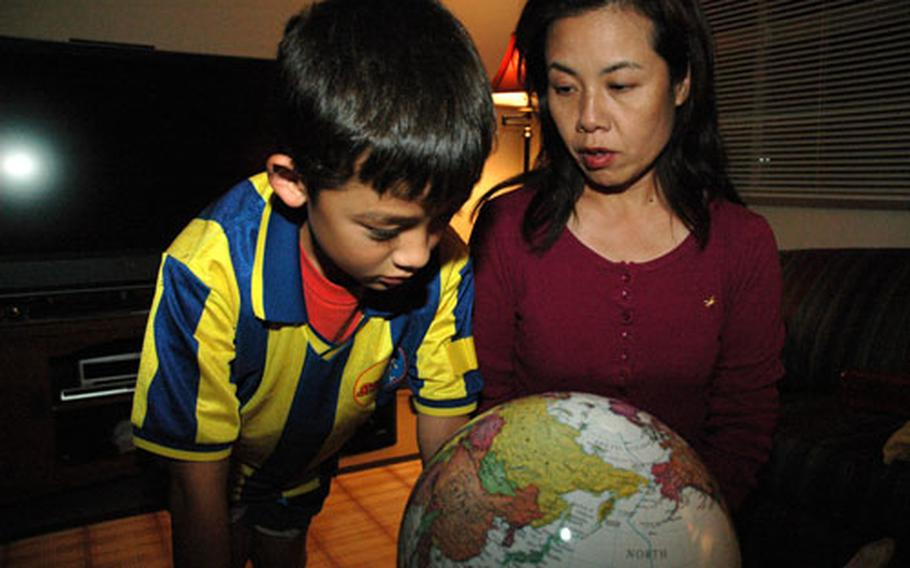 Luke Ruby, 9, and his mother, Hiroe Ruby, use a computerized globe to study about different countries around the world. Hiroe is Japanese and Luke's father, Gunnery Sgt. Troy Ruby, is American. Luke has gone to a mixture of Japanese and American schools, and this year he's in fourth grade at MC Perry Elementary School at Marine Corps Air Station Iwakuni.