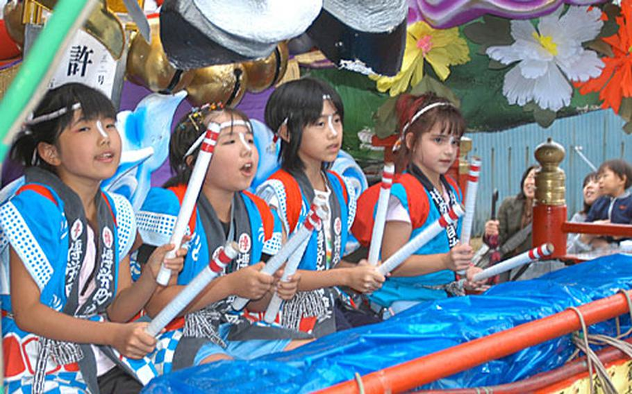 Emily Reams, 8, far right, plays the taiko drums while sitting on a parade float during a festival Sept. 2 in the northern Japan town of Gonohe. Reams, whose parents work on Misawa Air Base, was the only American playing taiko in the festival. Reams has attended Japanese school since the age of 3 and is fluent in the language.