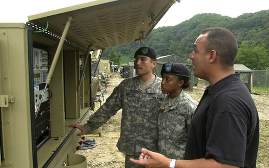 Contractor Kevin Cruz of Datapath, right, talks with Sgt. Peter Scales and Pvt. Jessica Hutchins of 4th Battalion, 2nd Attack Aviation, about the new system for field communication at Camp Hovey.