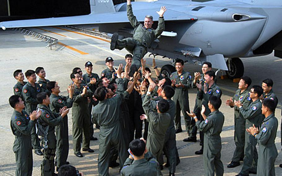 Before returning to the States, Maj. Craig Vincent is thrown into the air by some of the South Korean pilots who he instructed. The nine-month training program, centering around the F-15K, concluded last week.