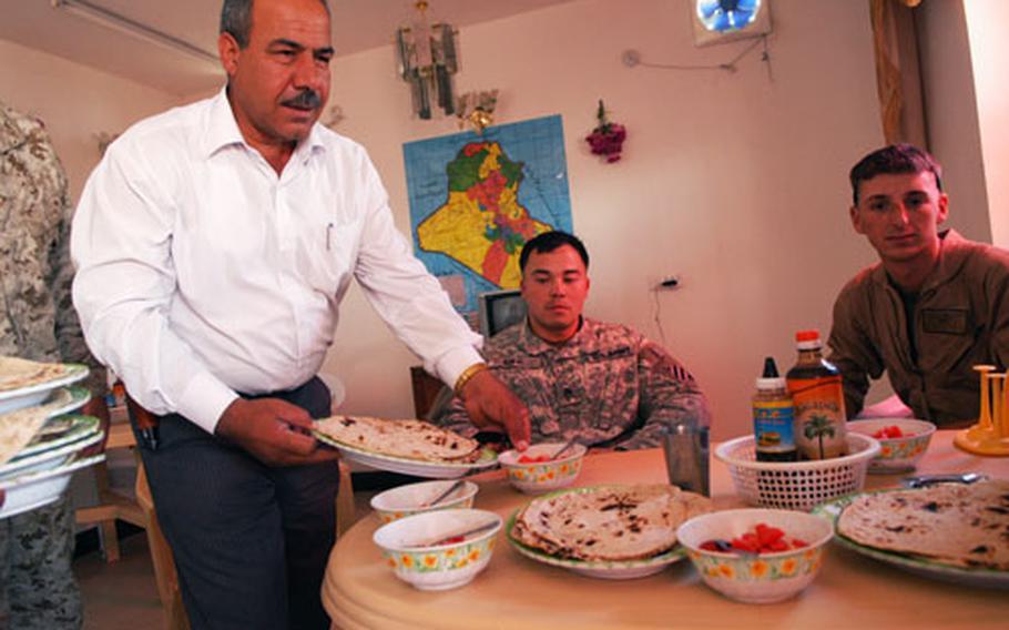 Owner Ali Jassam serves clientele kebabs at his Anbar province restaurant.