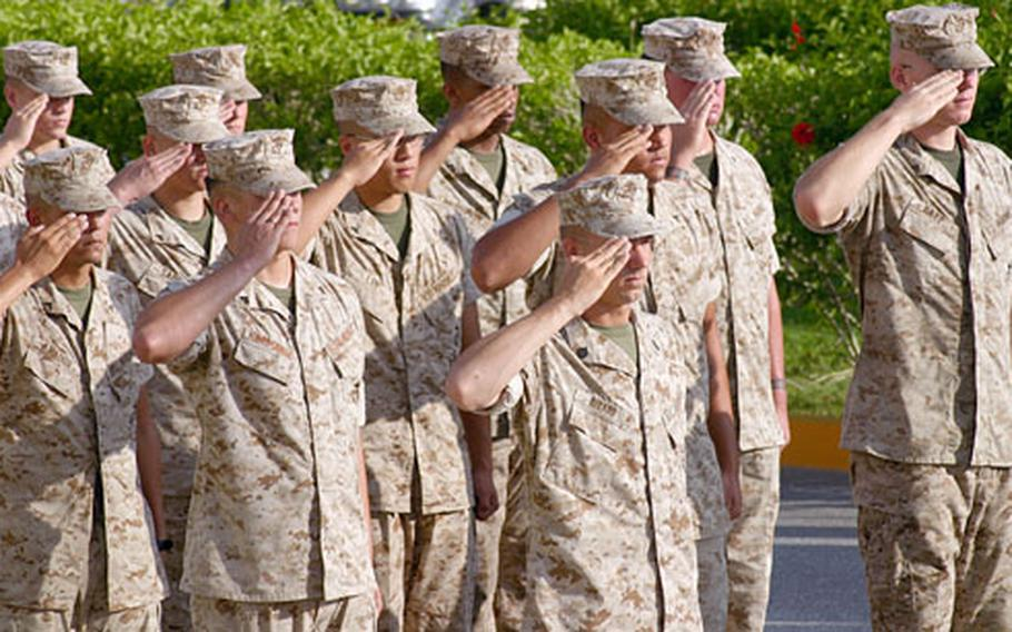 Marines salute during the morning colors that started 3rd Marine Division's 65th anniversary ceremony Monday on Camp Courtney, Okinawa.