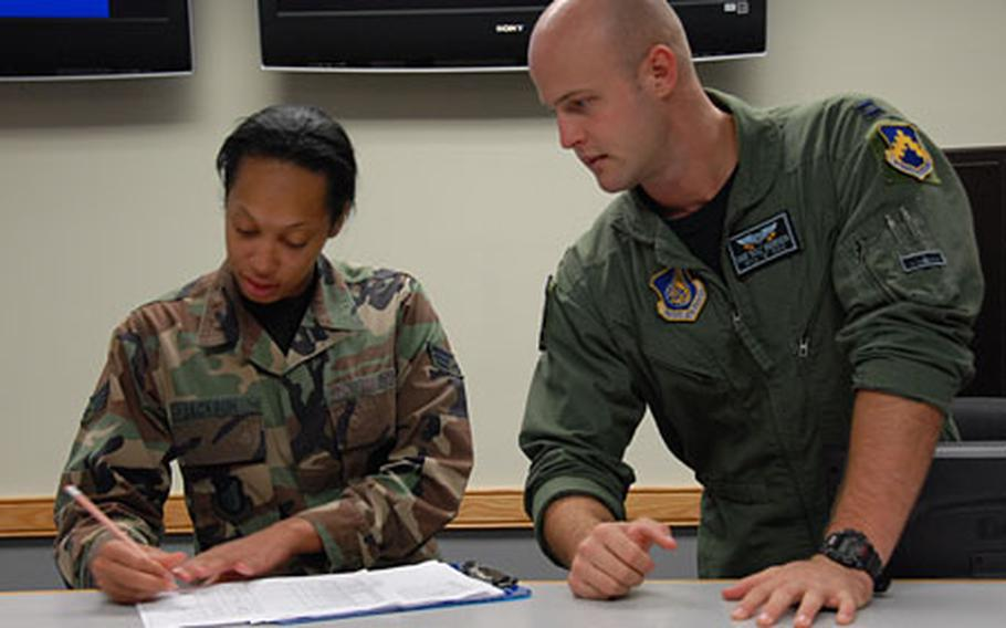 """Capt. Dave """"Bull"""" Anderson, right, talks with Senior Airman Jamilya Jackson at Kunsan Air Base, South Korea, earlier this month. Anderson, an F-16 pilot, was awarded the Distinguished Flying Cross last month for killing six insurgents who were attacking American troops on the ground during a 2006 deployment to Iraq."""