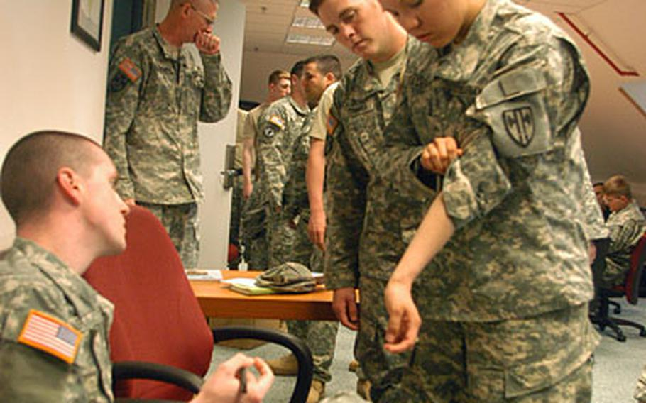 Pvt. Emily Faden, right, of 1st Platoon, 554th Military Police Company, shows where she received a tuberculosis detection shot to Sgt. Justin Rash, a medic with the Patch Health Clinic. The shots were given to determine whether Faden and other soldiers had contracted TB during their 15-month deployment to Iraq.