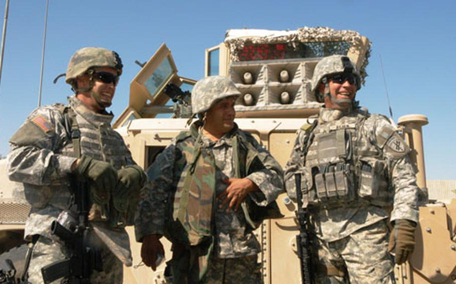 From left to right, U.S. Army Sgt. Stephen M. Burnham, interpreter Abraham Khadir and Sgt. Jeff Reick stand in front of their PSYOP loudspeaker Humvee in Fallujah, Iraq.