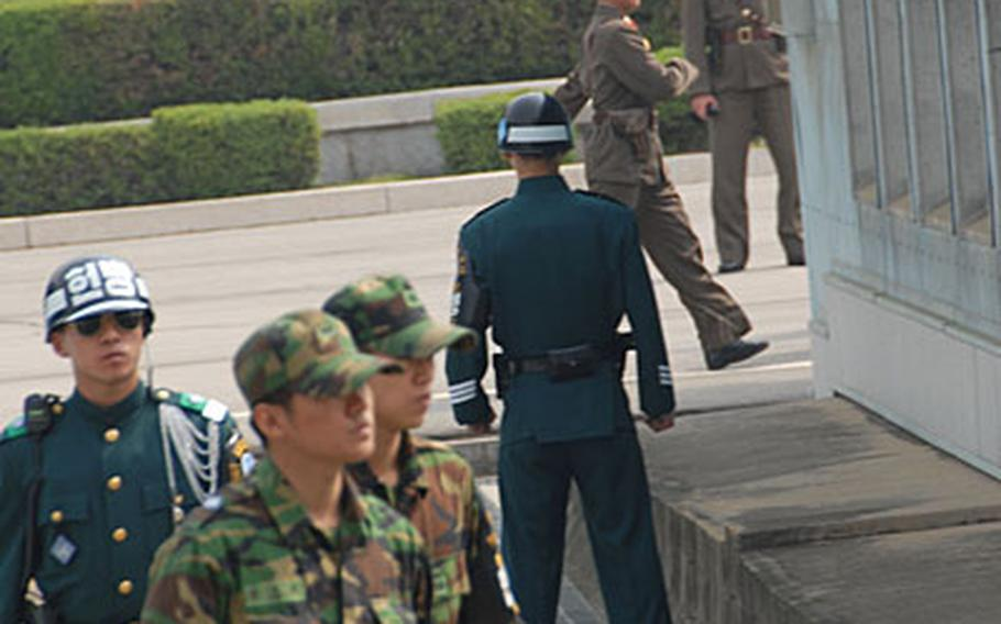 In this May file photo, South Korean and North Korean guards patrol the Demilitarized Zone near Panmunjom before South Korean officials crossed into North Korea for a meeting. According to South Korean news reports, President Roh Moo-hyun will propose during an inter-Korean summit next week that both countries withdraw their guards from the border.