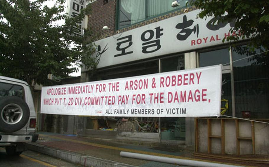 A banner outside the Royal beauty shop near Camp Hovey's gate in Dongducheon, South Korea, shown in this Sept. 20 file photo, seeks compensation for a May 19 fire that some say was started by a U.S. soldier.
