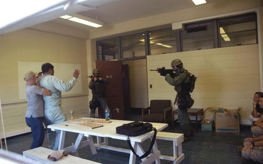 Marines of the Camp Foster, Okinawa, special reaction team face off with a mock terrorist, who was holding two hostages. Army officials hosted the terrorism drill at Port Naha on Okinawa.