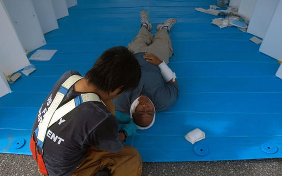 """A firefighter from the U.S. Army Fire Department treats an office worker """"wounded"""" in a mock suicide bomb attack."""