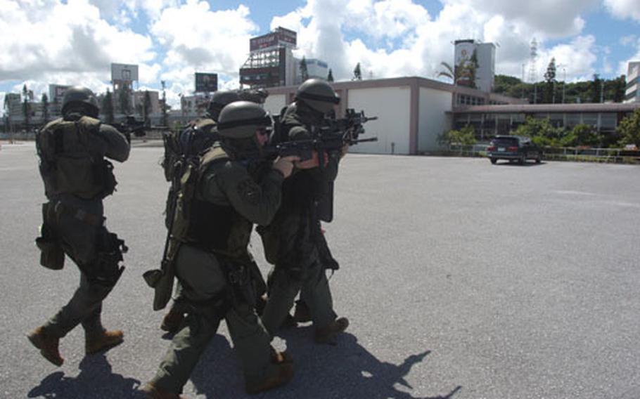 Marines of the Camp Foster, Okinawa, special reaction team assault across a parking lot toward a building where a mock terrorist was holding two hostages.