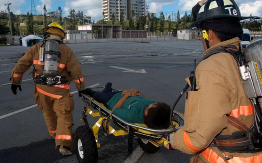 """Two firefighters rush a """"wounded"""" office worker to a temporary triage center for medical treatment."""