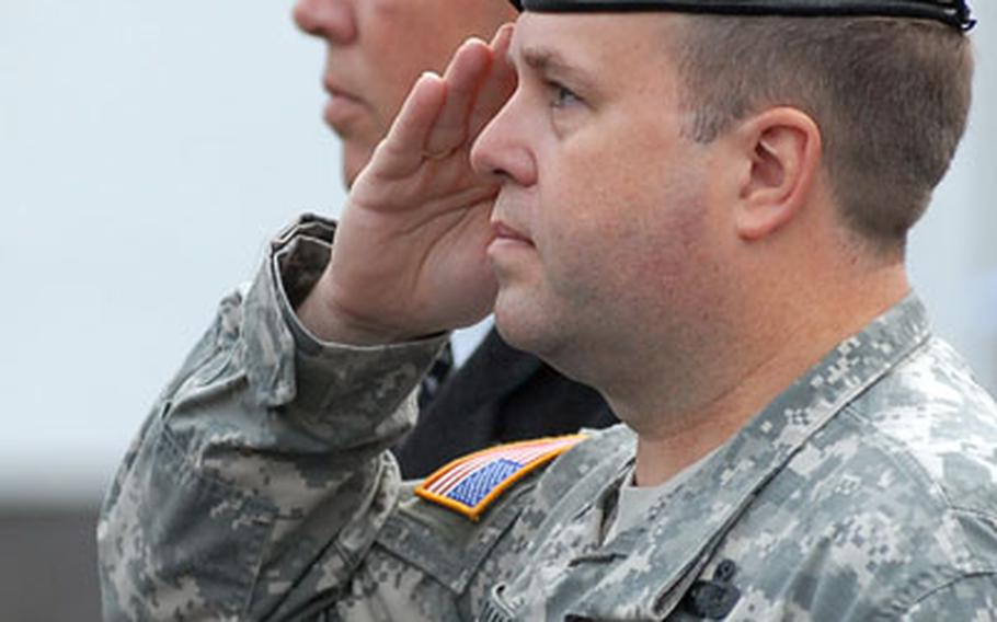 Col. Ray Graham Jr., commander of U.S. Army Garrison Wiesbaden, right, and Craig Brichard, the USAG Giessen manager salute the flag during the national anthem, during the closure ceremony. Giessen officially closed Friday, marking the end of an American military presence in the German city.