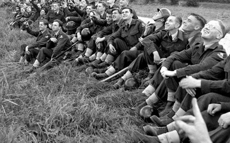 Dutch airmen line a canal near Nijmegen to watch air drops by American paratroopers in September, 1953.