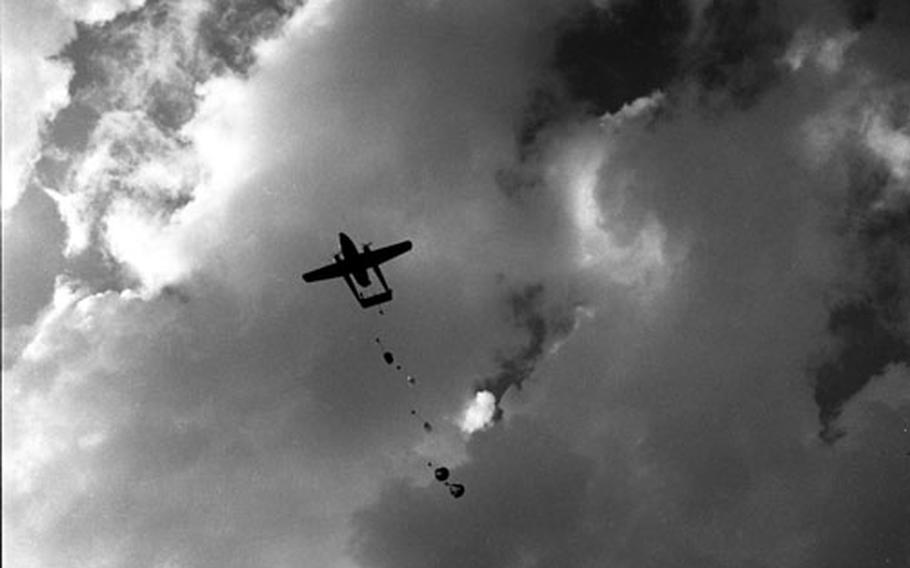 """American paratroopers jump from a C119 """"Flying Boxcar."""""""
