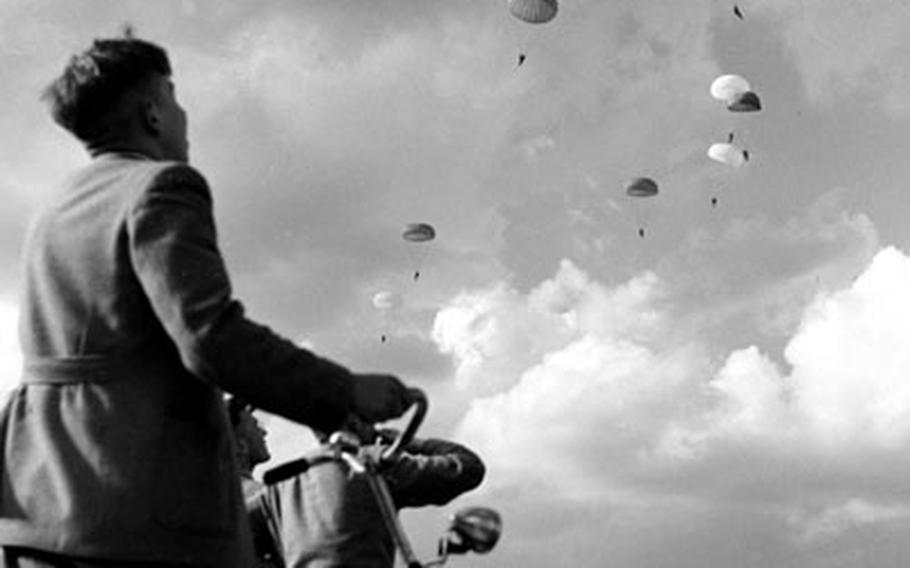 A Dutch boy watches the paratroopers glide to the ground.