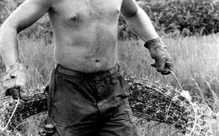 """A Seabee has no room for error as he carries a sharp, heavy coil of barbed wire while working on the """"Da Nang Line."""""""