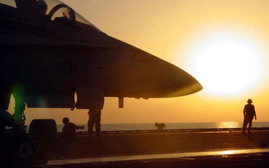 An F/A-18 Hornet aboard the USS Enterprise prepares to take off just before sunset in the Gulf of Oman. While a new Navy strategy calls for more humanitarian assistance missions, the aircraft carrier still provides a lethal punch from anywhere there is deep water.