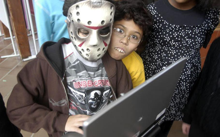 """Daniel """"Jason"""" Carmichael, left, and Tristan Reyes (wearing fake teeth), both fifth-graders at Patch Elementary School, used their computer to play sound effects Wednesday at the Halloween Readers Theater Fest."""