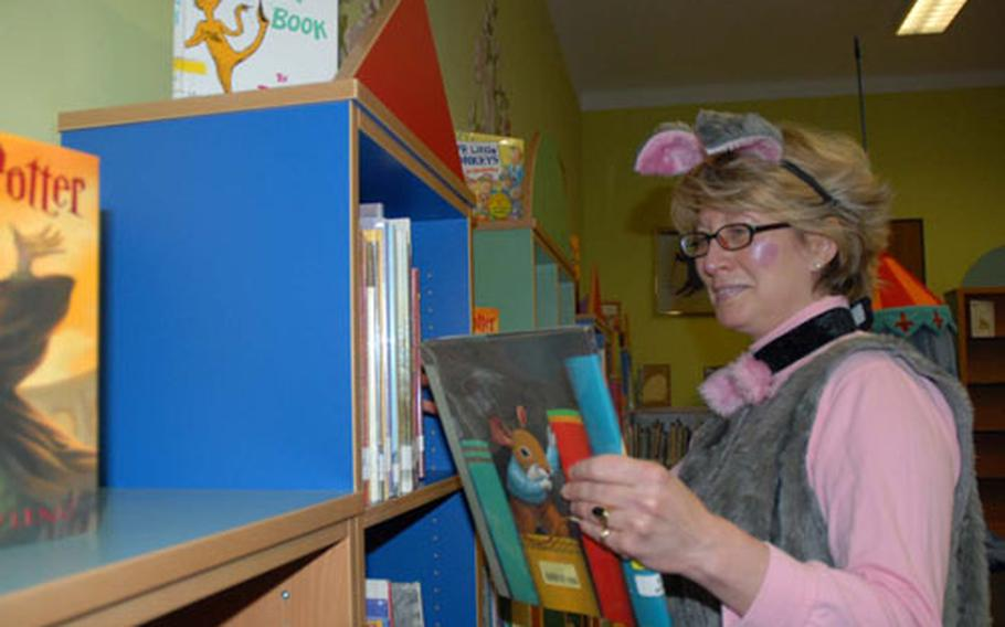 Dressed in her Library Mouse costume in preparation for the Halloween Harry Potter Costume Party, Karen Lazzeri, director of the Bamberg, Germany, Community Library, shelves books in the library's children's room. Lazzeri and her staff were recently honored for having the Army's top medium-size installation library for the second year in a row.
