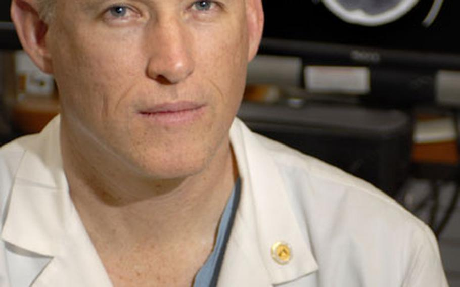 Army Dr. (Col.) Stephen Flaherty, Chief of Trauma at Landstuhl Regional Medical Center, poses for a portrait in front of a severe traumatic brain injury CT scan at Landstuhl.